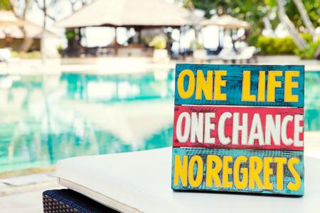 Inspiratie Motiverend Life Quote houten plank One Life One Chance Geen spijt op de zomer, tropisch zwembad achtergrond kopie ruimte