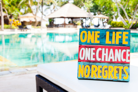 Inspirational Motivational Life Quote wooden board One Life One Chance No regrets on summer, tropical swimming pool background Copy space