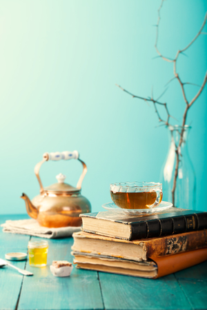 kinfolk: Cup of tea with teapot and vintage books on wooden table Blue background Stock Photo