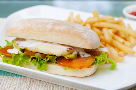 haloumi: Vegetarian Ciabatta with tomatoes, grilled cheese haloumi, avocado and lettuce with french fries on white plate Summer background
