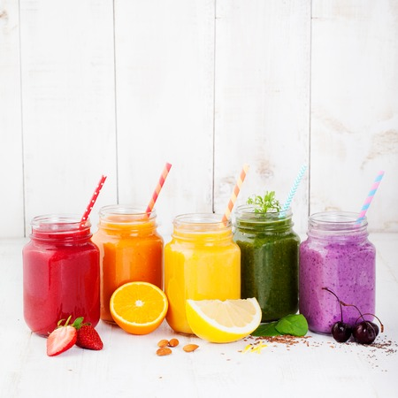 Smoothies, juices, beverages, drinks variety with fresh fruits and berries on a white wooden background. 写真素材