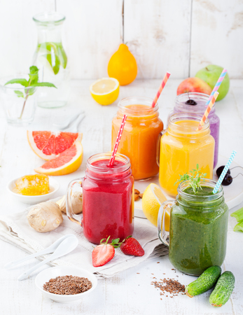 Smoothies, juices, beverages, drinks variety with fresh fruits and berries on a white wooden background. Standard-Bild