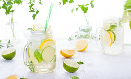 Lemonade with ice, lemon and lime slices in a jar with straw in a white summer wooden background