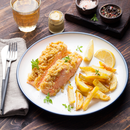 crumple: Fish salmon with crumple on top with baked potatoes and lemon slices on a wooden background