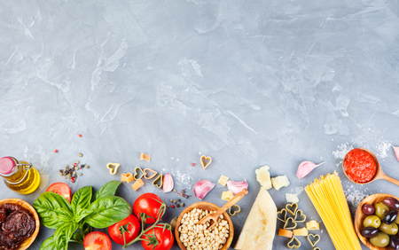 Italian food background with vine tomatoes, basil, spaghetti, olives, parmesan, olive oil, garlic Ingredients on stone table Copy space Top view Фото со стока
