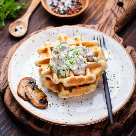 sauce dish: Savory waffles with corn and mushroom creamy sauce on a plate on a wooden background Top view