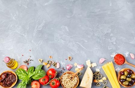 jitomates: Fondo de la comida italiana con tomates, albahaca, espaguetis, aceitunas, queso parmesano, aceite de oliva, ajo Ingredientes en mesa de piedra Copia espacio Vista superior