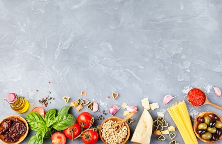 Italian food background with vine tomatoes, basil, spaghetti, olives, parmesan, olive oil, garlic Ingredients on stone table Copy space Top view Stock Photo
