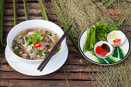 hoisin: Traditional Vietnamese beef soup pho with sous Hoisin on a wooden background Copy space