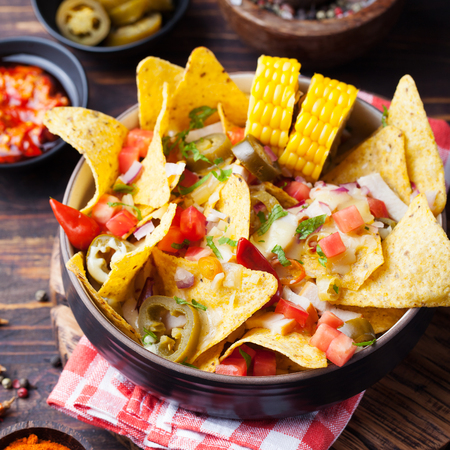 red food: Nachos with melted cheese sauce, salsa and corn cobs in bowl on brown wooden background Top view