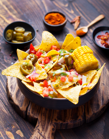 tex mex: Nachos with melted cheese sauce, salsa and corn cobs in bowl on brown wooden background Top view