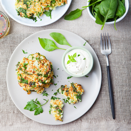 fritter: Cabbage and spinach pancakes with yogurt dressing with fresh herbs Top view Stock Photo