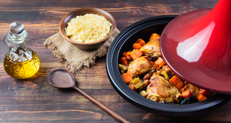 Tagine with cooked chicken and vegetables. Traditional moroccan cuisine. Wooden background Copy space