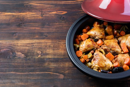 rustic food: Tagine with cooked chicken and vegetables. Traditional moroccan cuisine. Wooden background Copy space