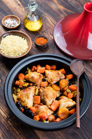 moroccan cuisine: Tagine with cooked chicken and vegetables. Traditional moroccan cuisine. Wooden background Copy space