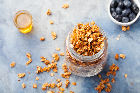 healthy snacks: Healthy breakfast Fresh granola, muesli with berries, honey in a glass jar on a stone background Copy space