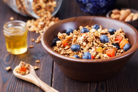 Gesundes Frühstück. Frisches Müsli, Müsli mit Beeren, Honig und Milch in einer Holzschale auf einem hölzernen Hintergrund Draufsicht