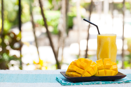 Fresh tropical fruit smoothie mango juice and fresh mango on a outdoor tropical background Copy space 스톡 콘텐츠