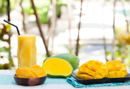 Fresh and dried mango fruit with smoothie juice on a outdoor tropical background Copy space