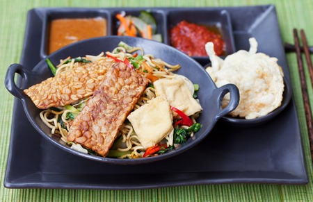 mie noodles: Mi goreng,mee goreng Indonesian cuisine, spicy stir fried noodles with tempeh and assortment of asian sauces Stock Photo