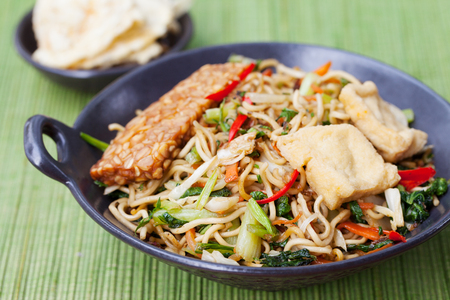 goreng: Mi goreng,mee goreng Indonesian cuisine, spicy stir fried noodles with tempeh and assortment of asian sauces Stock Photo