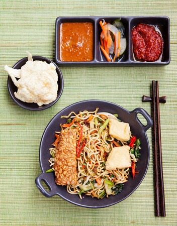mi: Mi goreng,mee goreng Indonesian cuisine, spicy stir fried noodles with tempeh and assortment of asian sauces Top view Stock Photo