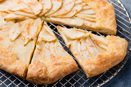 jewish home: Apple galette, pie, tart with cinnamon on cooling rack on a blue stone background.