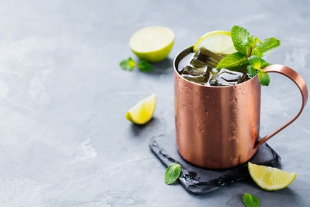 cold background: Cold Moscow Mules cocktail with ginger beer, vodka, lime Grey stone background. Copy space