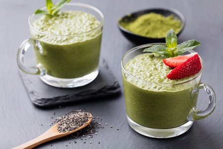 Matcha green tea chia seed pudding, dessert with fresh mint and strawberry on a black slate background Healthy breakfast