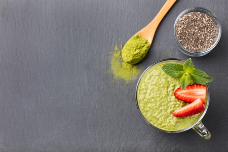 Matcha green tea chia seed pudding, dessert with fresh mint and strawberry on a black slate background. Healthy breakfast Stock Photo
