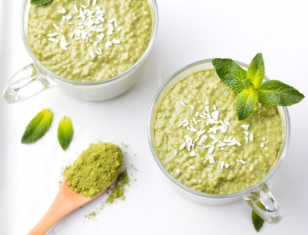 Matcha green tea chia seed pudding, dessert with fresh mint and coconut on a white stone background Healthy breakfast. Top view Copy space
