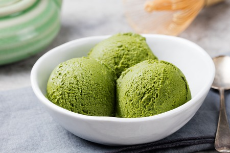 Green tea matcha ice cream scoop in white bowl on a grey stone background. Stock Photo