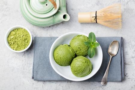 comiendo helado: Verde matcha té una cuchara de helado en un recipiente blanco sobre un fondo gris piedra. Espacio de la copia. Vista superior