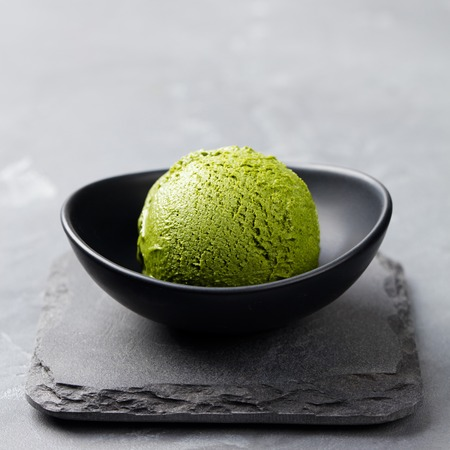 Green tea matcha ice cream scoop in bowl on a grey stone background Stockfoto