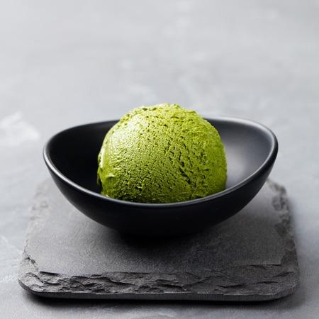 Green tea matcha ice cream scoop in bowl on a grey stone background Foto de archivo