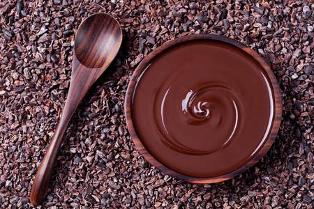 Kom met gesmolten chocolade en een houten lepel op een gemalen rauwe cacaobonen, nibs achtergrond. Kopieer de ruimte Bovenaanzicht ..