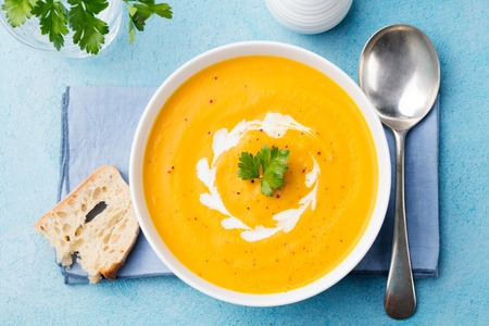 Pumpkin and carrot soup with cream and parsley on blue stone background Top view Standard-Bild