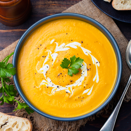 Pumpkin and carrot soup with cream and parsley on dark wooden background Top view.