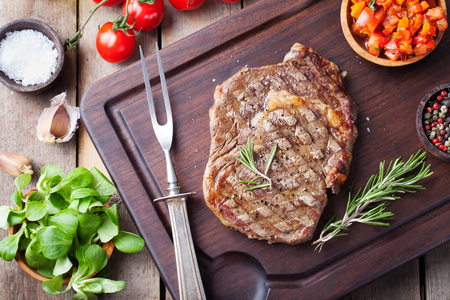Beef steak with cherry tomato and rosemary on a dark cutting board Wooden background Top view Copy space