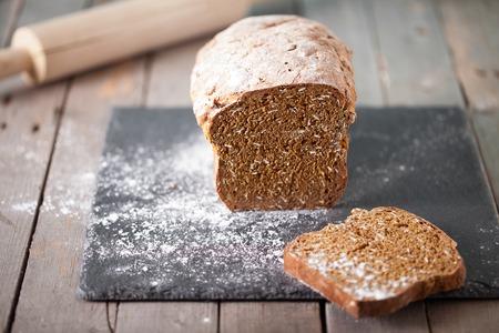 pain: Pain frais de soude irlandais avec l'avoine en tranches sur une planche à découper en ardoise fond en bois espace copie mise au point sélective Banque d'images