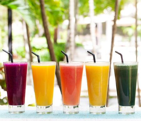 rainbow cocktail: Assortment juices, smoothies, beverages, drinks variety on a outdoor tropical background Copy space Stock Photo