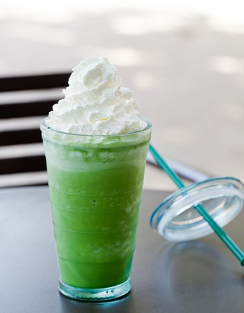Iced matcha green tea latte, frappe Outdoor summer tropical background Copy space