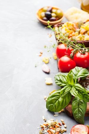 Fondo de comida italiana con vid tomates, albahaca, spaghetti, aceitunas, parmesano, aceite de oliva, ajo Ingredientes en la mesa de piedra Copia espacio Vista superior