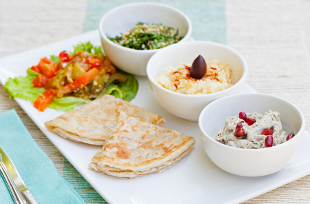 tabbouleh: Assortment of dips: hummus, chickpea dip, tabbouleh salad, baba ganoush and flat bread, pita on a plate. Summer outdoor background Stock Photo