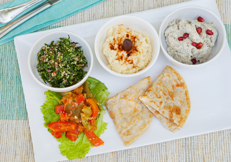 tabbouleh: Assortment of dips: hummus, chickpea dip, tabbouleh salad, baba ganoush and flat bread, pita on a plate. Summer outdoor background Top view Copy space
