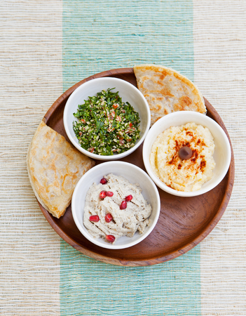 tabbouleh: Assortment of dips: hummus, chickpea dip, tabbouleh salad, baba ganoush and flat bread, pita on a plate. Summer outdoor background Copy space Stock Photo