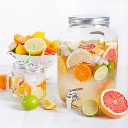 Detox fruit infused flavored water, lemonade, cocktail in a beverage dispenser with fresh fruits Cleanse body and burn fat