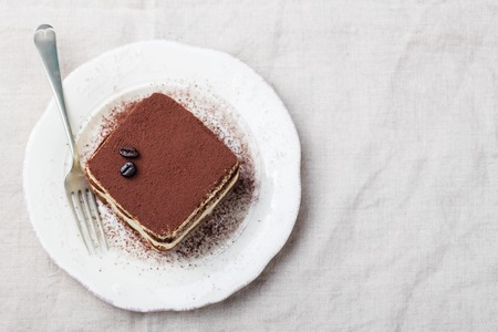 Tiramisu, traditional Italian dessert on a white plate Top view Copy space 免版税图像
