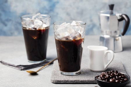 Ice coffee in a tall glass and coffee beans on a grey stone background Archivio Fotografico