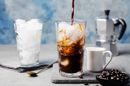 Ice coffee in a tall glass and coffee beans on a grey stone background 스톡 콘텐츠